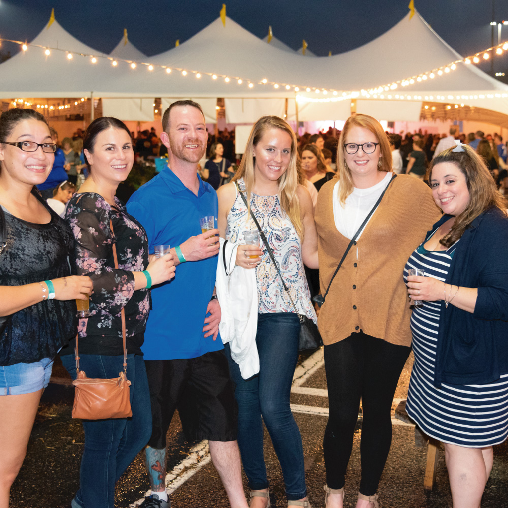 six people smiling for photo at beerfest outside